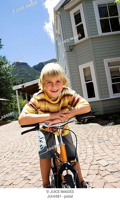 Blonde boy 4-6 leaning on bicycle in driveway, smiling, front view, portrait tilt