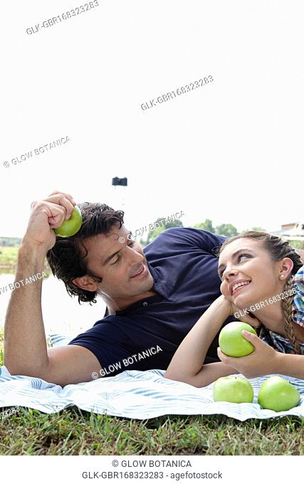 Couple lying on a blanket and eating apples