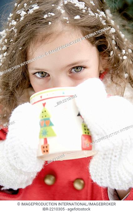 Girl with snowflakes in her hair drinking from a cup with a Christmas motif