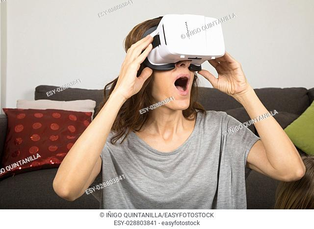 brown hair adult woman with virtual reality headset, or 360 glasses, grey shirt, open mouth amazed face expression, indoor home