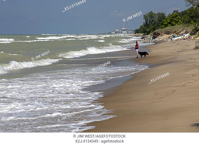 Beverly Shores, Indiana - A woman walks her dog on the beach of Indiana Dunes National Lakeshore, at the southern end of Lake Michigan