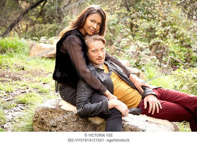 Man lying on woman's lap on rock