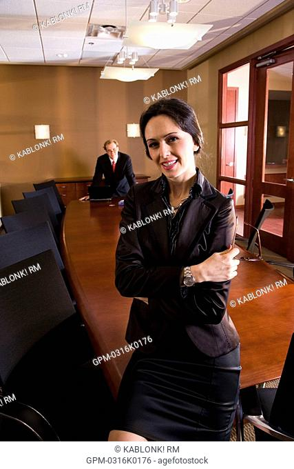 Portrait of smiling businesswoman in boardroom, man in background