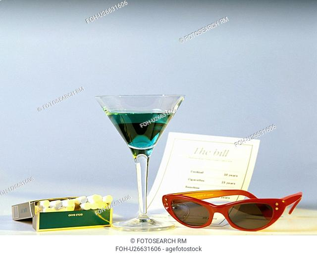 Green coloured cocktail with red sunglasses and cocktail cigarettes along with the bill