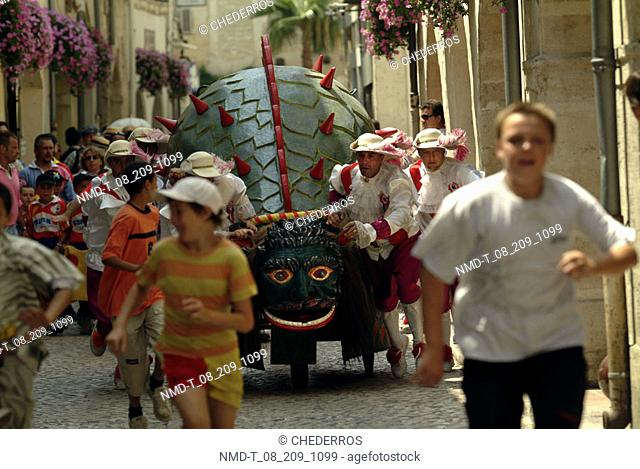 Group of people pushing a wooden dragon, Provence, France
