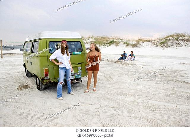 Portrait of young women in hippie fashion standing by van at beach
