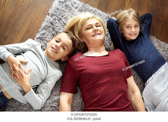 Grandmother and grandchildren relaxing on carpet