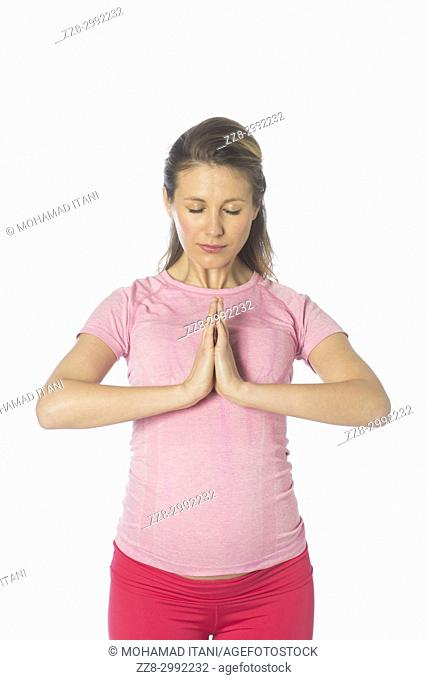Pregnant woman doing yoga against a white background