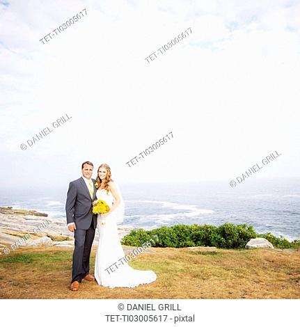 Portrait of married couple, sea in background