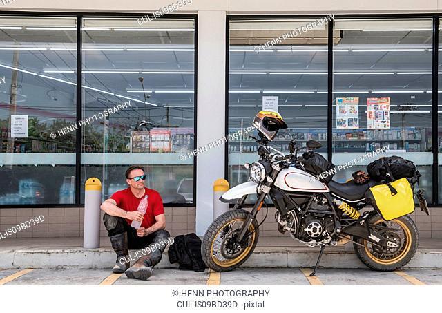 Man taking break in front of shop, Pattaya, Chonburi, Thailand