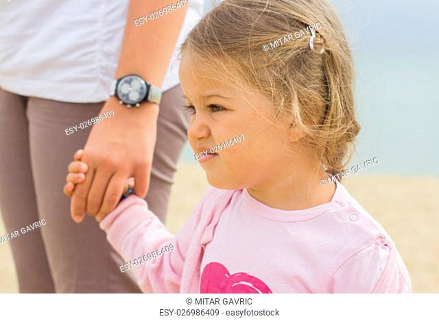 Portrait of little girl holding mother's hand, family lifestyle