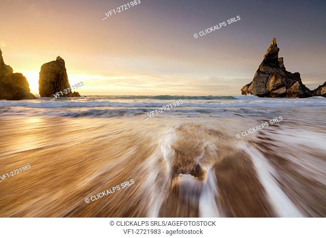 Ocean waves crashing on the beach of Praia da Ursa at sunset surrounded by cliffs Cabo da Roca Colares Sintra Portugal Europe