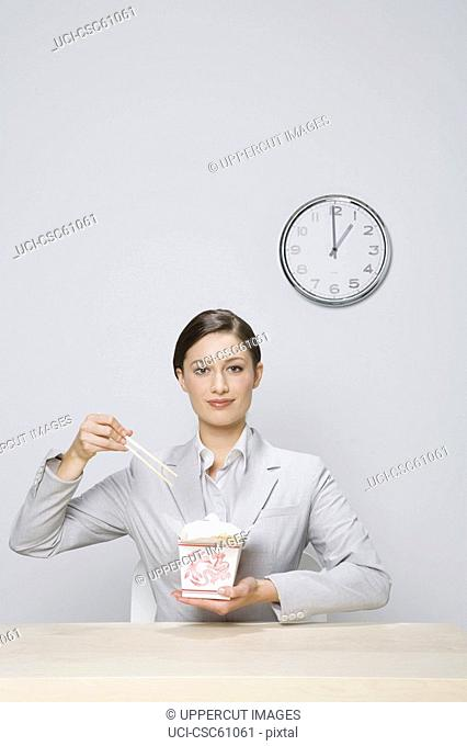 Businesswoman eating take out food