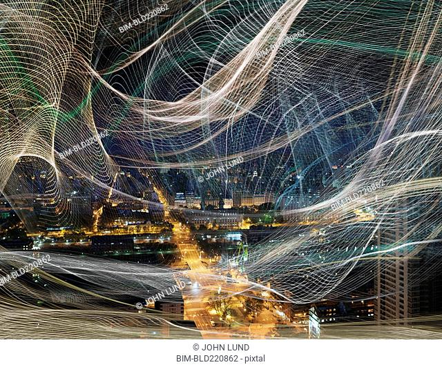 Light streams over cityscape at night