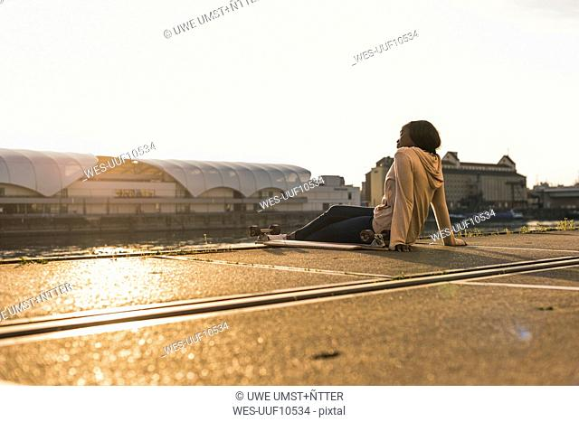 Young woman sitting at the river, watching sunset