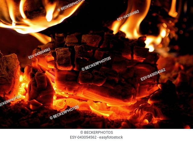 Close up of hot coals burning in a wood stove
