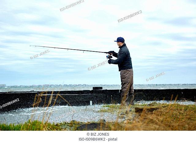 Young man sea fishing at water's edge