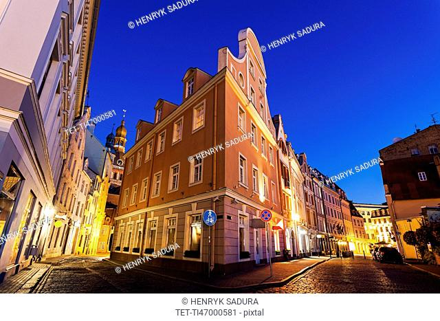 Corner of illuminated building against blue dusk sky