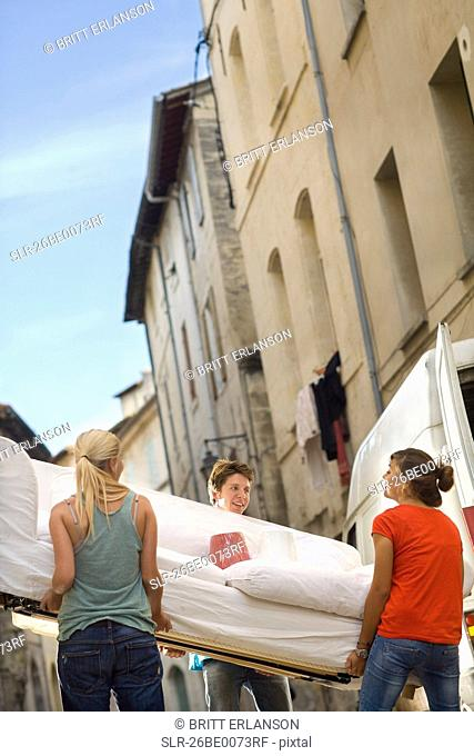 Friends move couch in street