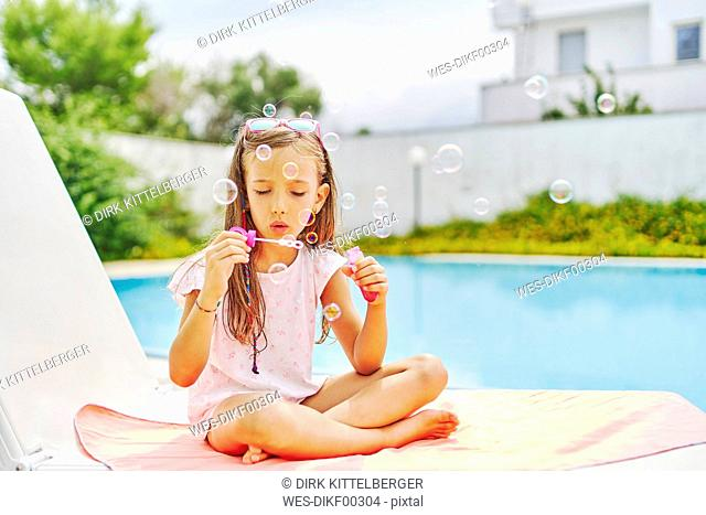 Girl blowing soap bubbles at the poolside