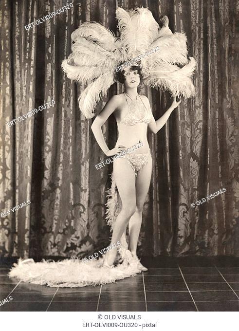 Showgirl wearing feather headdress and sequined bikini