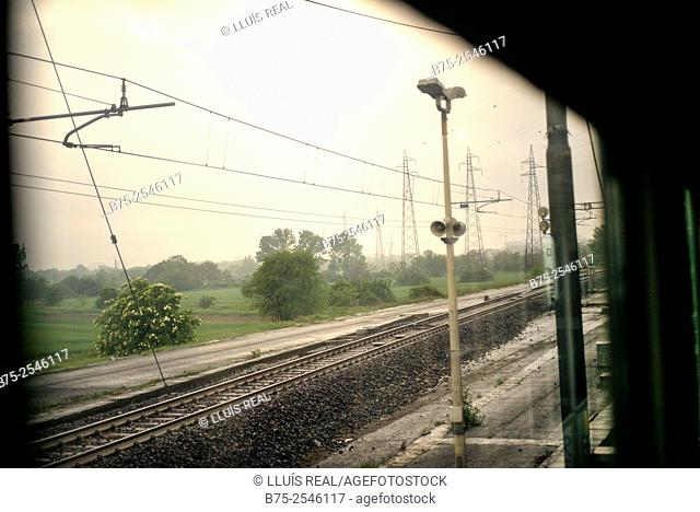 View from the window of the train car of the field landscape with trees, electrical towers, lamppost, and railways, passed through a station bound for Milan