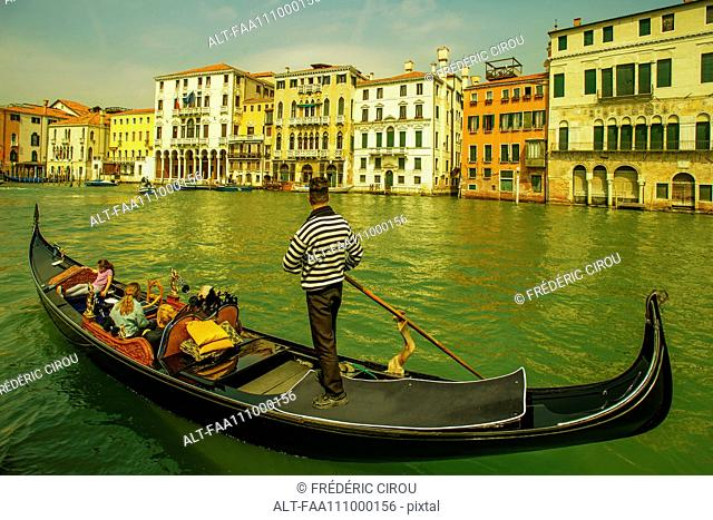 Tourists enjoy a gondola ride on the Grand Canal in Venice, Italy