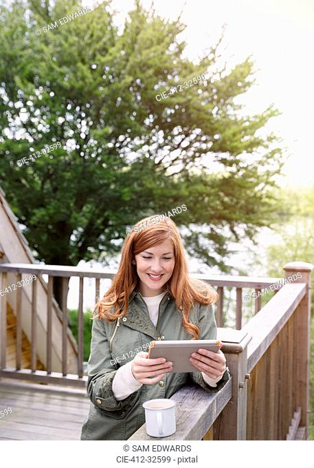 Smiling woman with red hair using digital tablet on cabin balcony