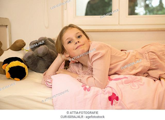 Portrait of mischievous girl lying on bed
