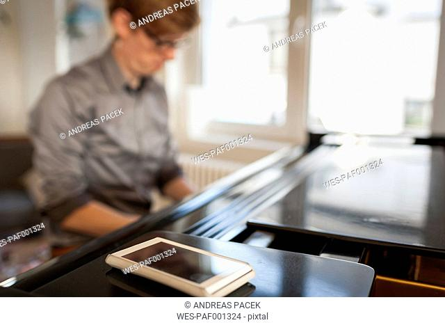 Man playing grand piano with cell phone in foreground
