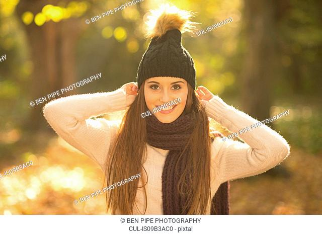 Portrait of young woman in forest, wearing knitted hat and scarf