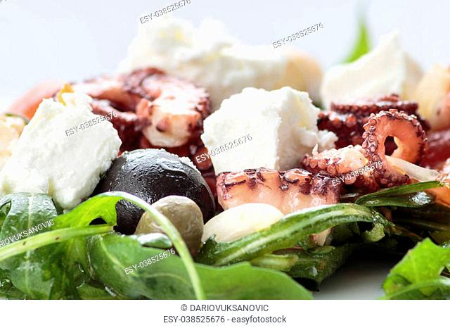 Octopus salad with rucola, olives and feta cheese on white plate