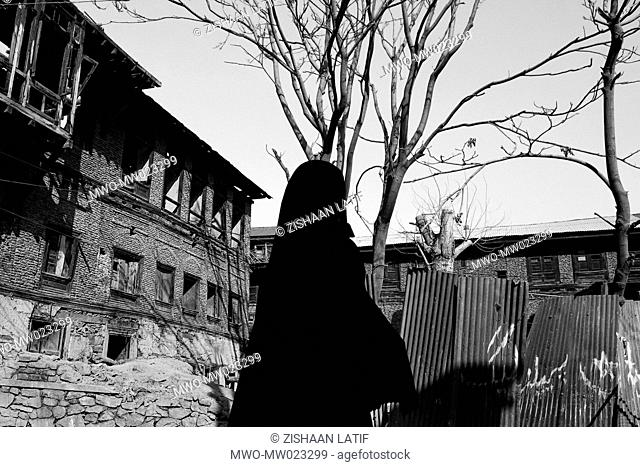 A veiled woman walks past a destroyed house in the infamous 'Downtown' area, which previously housed insurgents that used these areas for propaganda Srinagar