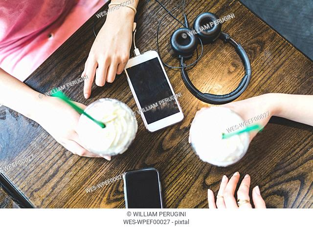 Two women at table with milkshakes, cell phones and headphone