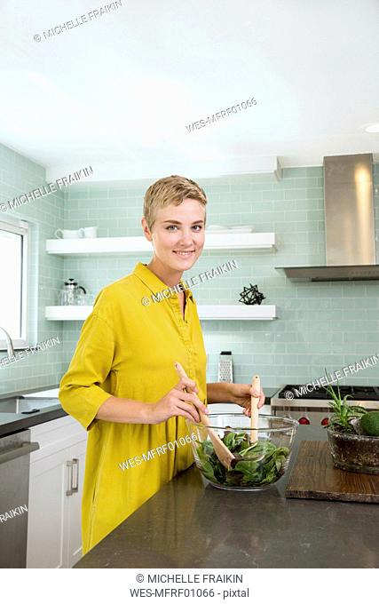 Portrait of smiling young woman preparing salad in kitchen