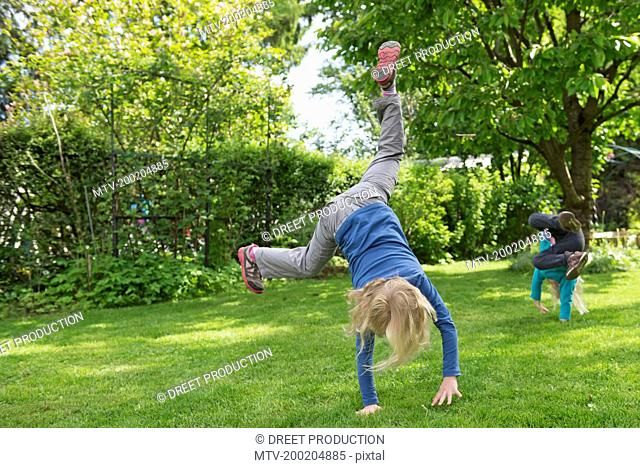 Two kids performing cartwheels on garden lawn