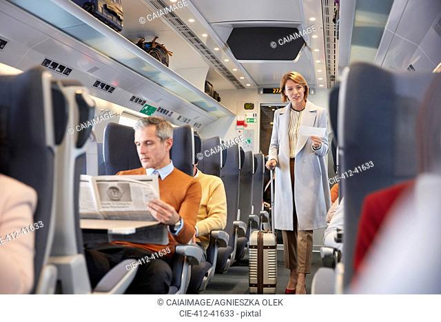 Businesswoman with ticket and suitcase boarding passenger train, looking for seat