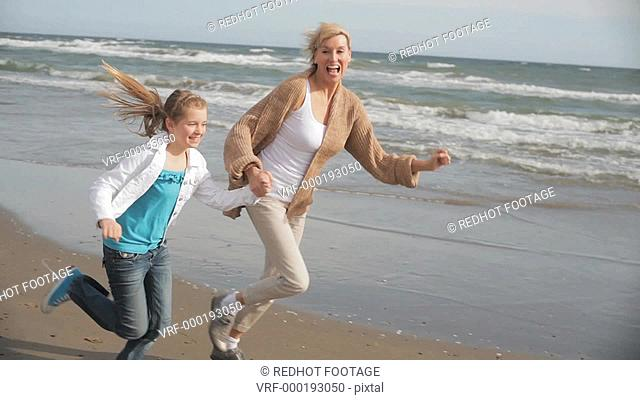 Grandmother and granddaughter running together on windy beach