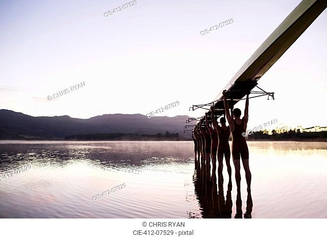 Rowing team entering lake at dawn with scull overhead