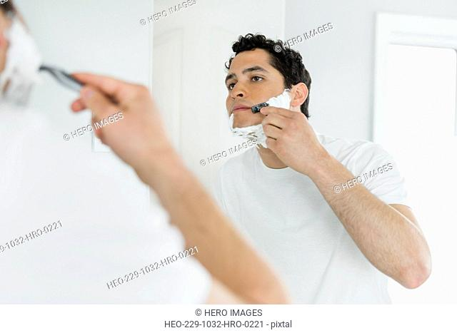 Young man shaving in domestic bathroom