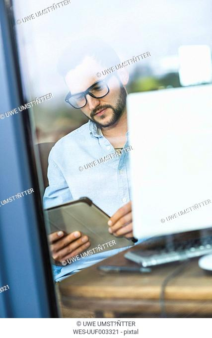 Young man behind windowpane looking at digital tablet