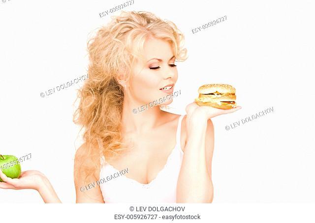 young beautiful woman choosing between burger and apple
