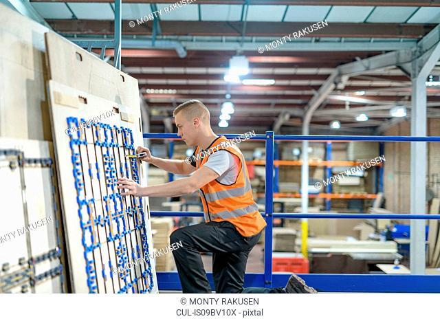 Worker checking cardboard cutter in cardboard box factory