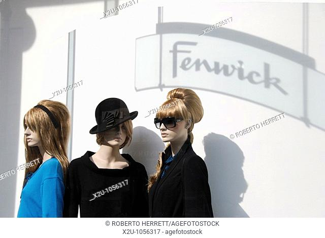 Three female mannequins dressed in fashionable clothes on display in Fenwick department store window, New Bond Street, London, England