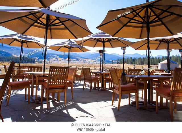 Umbrellas over outdoor patio dining area at a mountain resort lodge with scenic view of mountain range