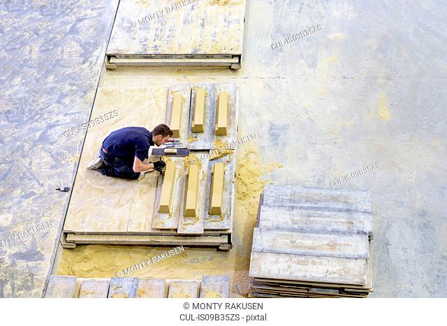 Overhead view of worker moulding stone in architectural stone factory