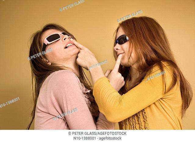 Preteen girls wearing sunglasses