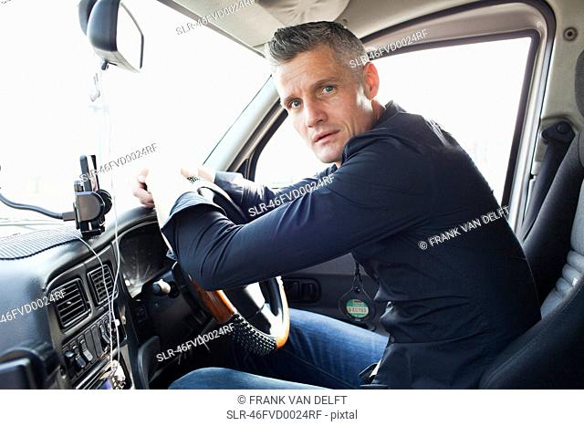 Taxi driver sitting at steering wheel