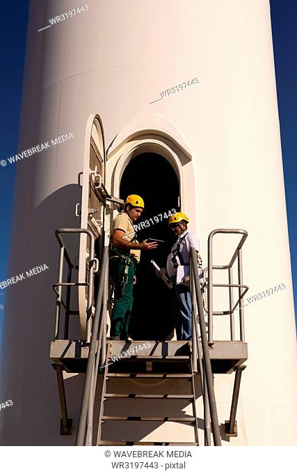 Engineers standing at the entrance of wind mill