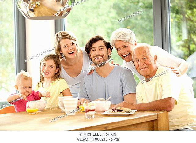 Portrait of happy extended family at breakfast table